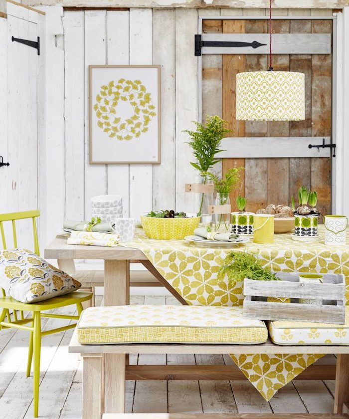 yellowish-green decorations, in a room covered in white wooden planks, wooden dining table and matching bench, acid green vintage chair, country kitchen décor, antique light brown wooden door
