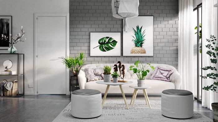 white wall with grey bricks, light cream sofa, living room color ideas, several potted plants, and two large, framed botanical artworks