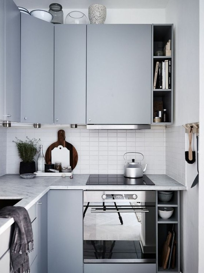 cabinets in duck's egg blue, inside small blue gray kitchen, with kettle and several vases, modern and functional