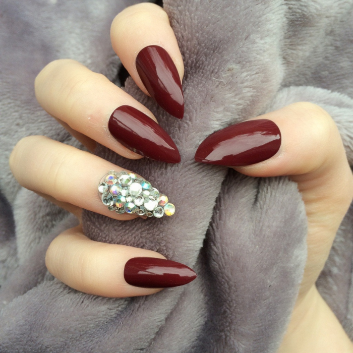 plush grey blanket, held by hand, with dark red nail polish, one nail is encrusted in silver, iridescent rhinestone stickers