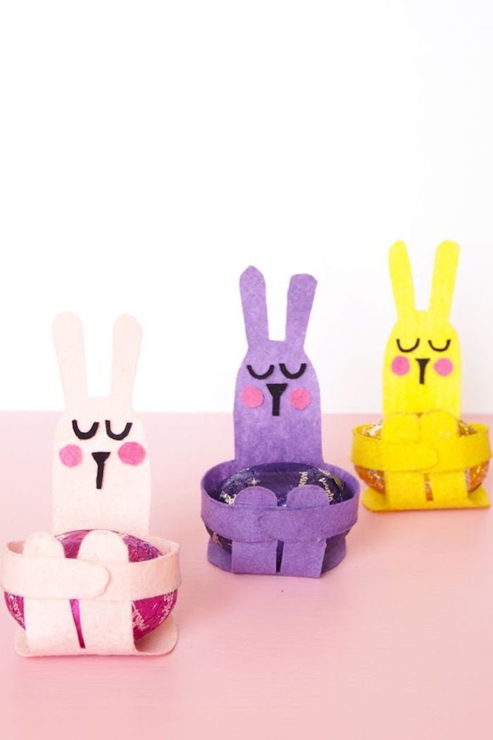 egg holders shaped like rabbits, made from pale pink, purple and yellow felt, with collaged faces, containing eggs in matching colors