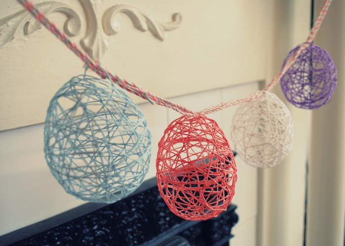 meshy and hollow, egg-shaped decorations, easter arts and crafts, made using balloons, glue and thread, hanging on a colorful rope, near a fireplace