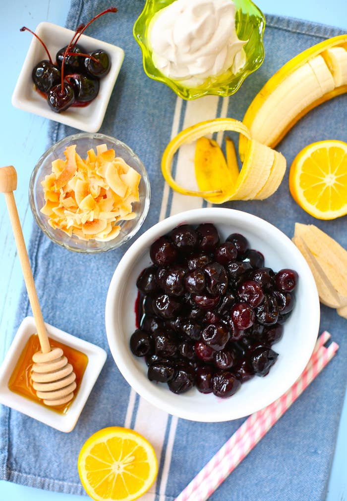 white bowl of maraschino cherries, placed on a table cloth, near cup of yoghurt, little plate with honey, peeled banana and cut lemon, toasted coconut flakes, healthy smoothie recipes