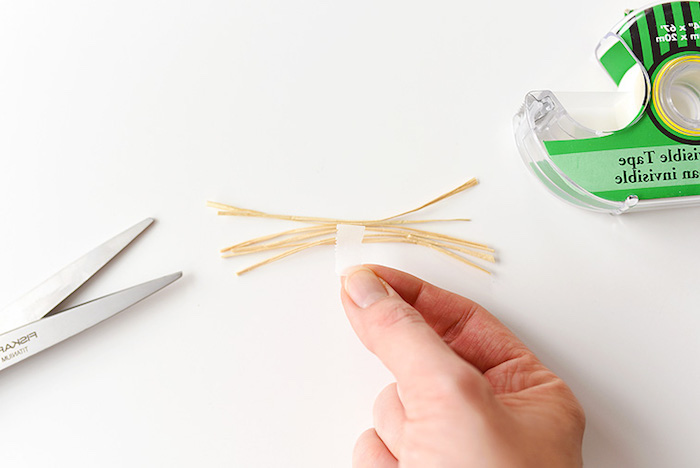 hand sticking a bunch of straw-like whiskers together, using white sticky tape, craft ideas for kids, sticky tape dispenser, and scissors nearby