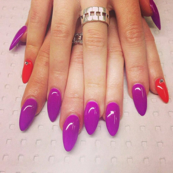 bright purple and red nails, smooth and long manicure, decorated with a few rhinestone stickers, on hands with chunky silver rings