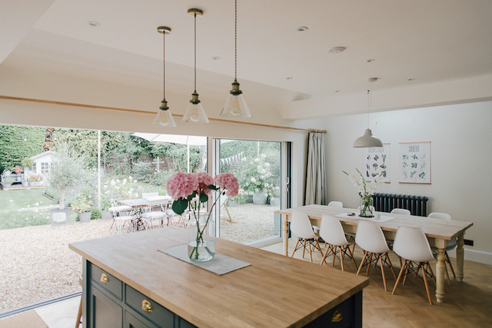 pink hydrangeas in a jar, on a dark green kitchen island, with light wooden top surface, rustic kitchen decor, dining room table, with eight white modern chairs in the background