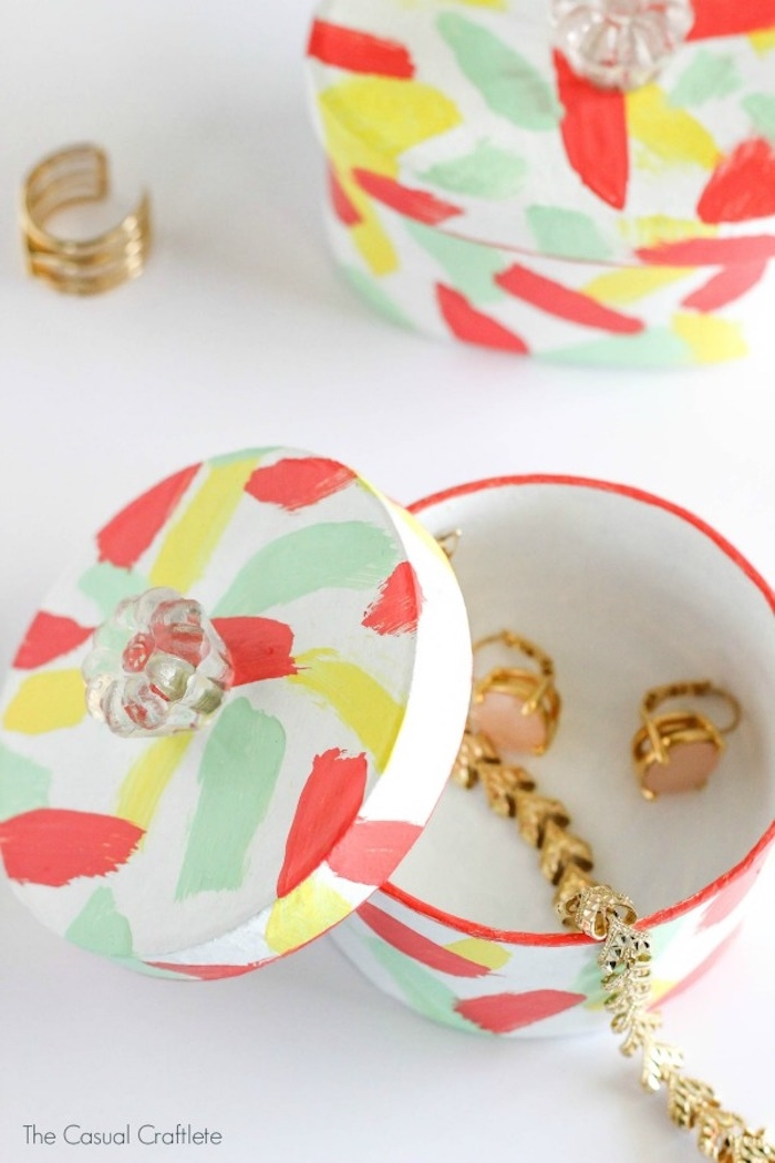 paint daubs in pale green, yellow and red, decorating round white jewelry box, with clear ornate handle, gift ideas for mom, golden earrings and bracelet