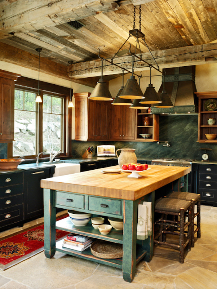 brown and black country kitchen cabinets, and a shabby chic wooden kitchen island, with two hand-made stools, inside room with wooden beams, and beige stone floor
