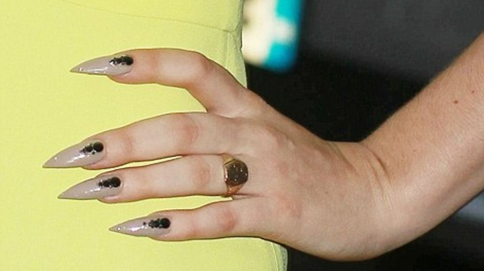 hand with large golden ring, and very sharp pointy nails, painted in beige nail-polish, and decorated with black details