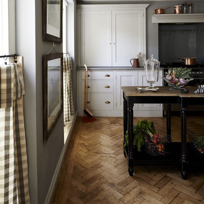 rustic country home décor, beige laminate floor, vintage wooden kitchen island, white cupboards and an antique stove, gingham curtains and two framed images