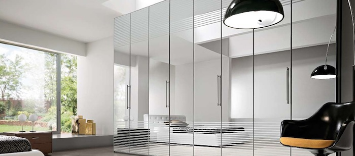 mirror covered closet, large with four or more doors, inside white bedroom, with bed and black modern chair, stylish wardrobes for a brighter home