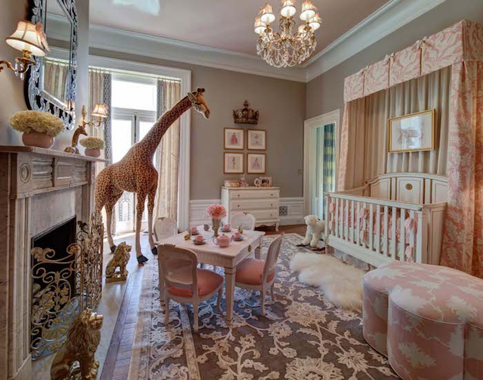 princess room for a baby, with big live-like giraffe toy, ornate carpet in gray and white, fireplace with golden details, white vintage crib, girl nursery themes