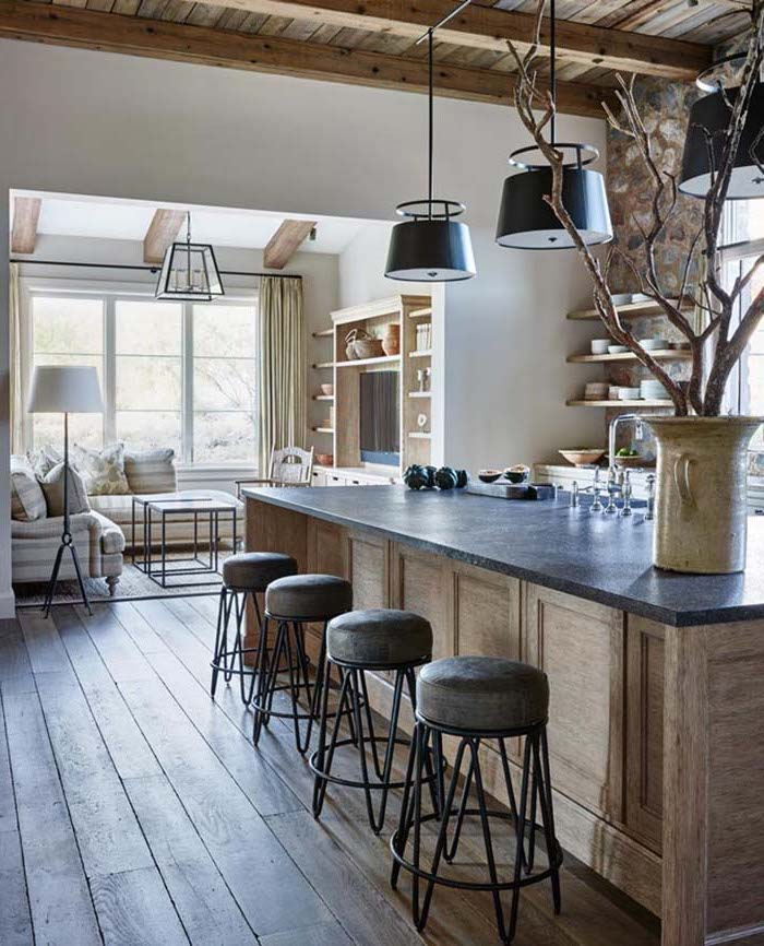massive wooden floorboards, inside open plan kitchen, with large kitchen island, stone-covered walls with shelves, and decorative tree in a large ceramic vase