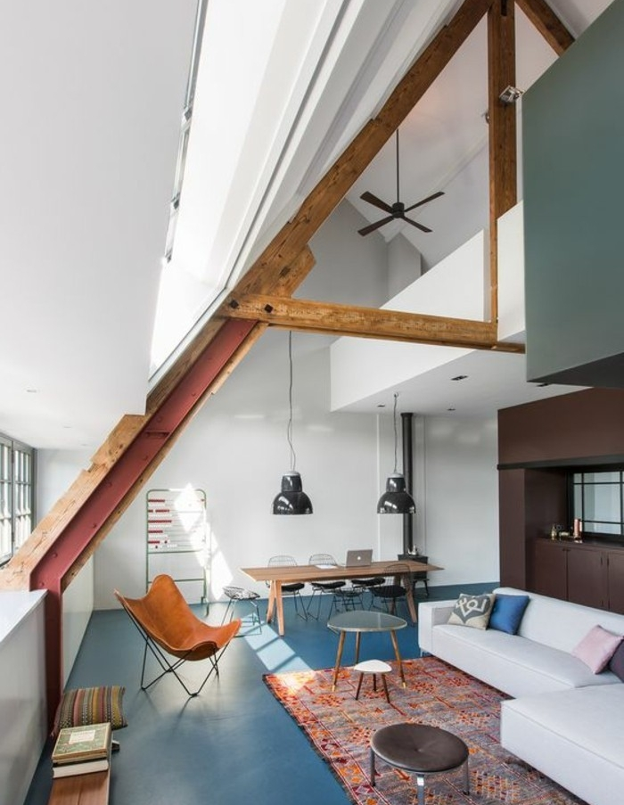 oriental multicolored rug, white sofa and dark brown cupboards, inside room with wooden beams on ceiling, and blue grey paint covering the floor