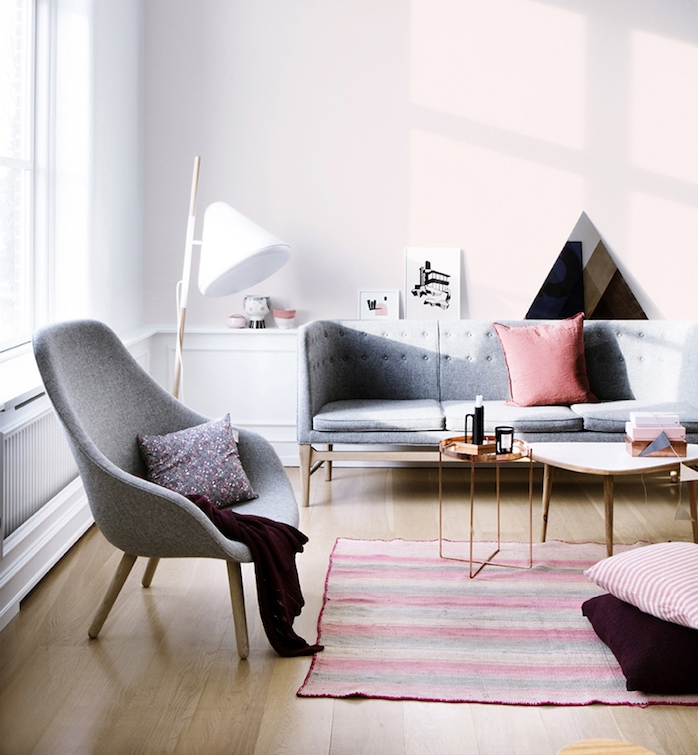 pinkish gray walls, with white paneling, light wooden laminate floor, pale gray sofa and armchair, colors that go with gray walls, striped rug, what colours look good with grey