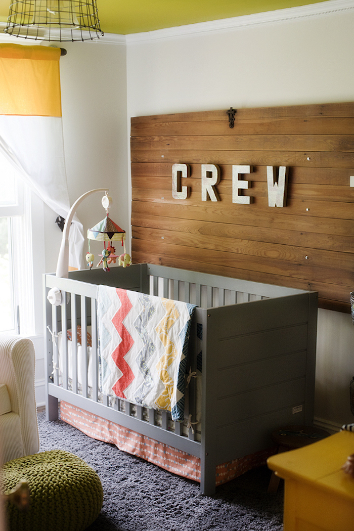 colorful mobile over gray wooden crib, boys room ideas, near white wall, with wooden board, decorated with pale gray letters, spelling the word crew
