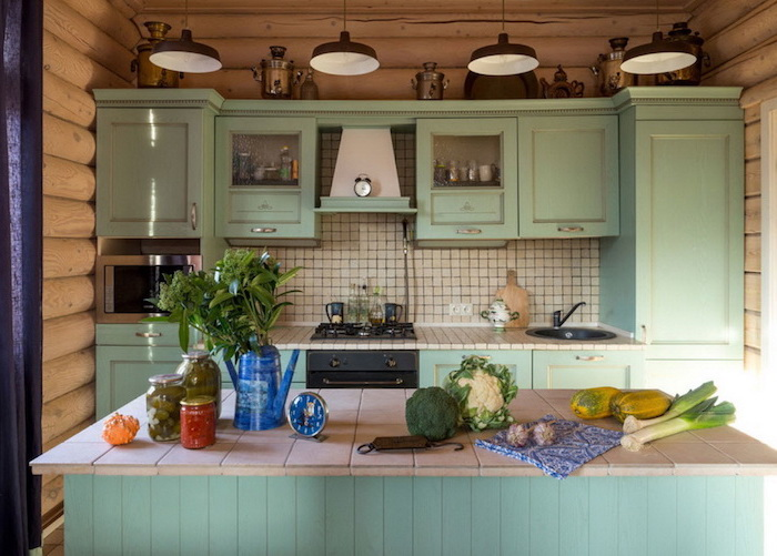minty green country kitchen cabinets, with a matching kitchen island, vegetables and canned preserves in jars, four hanging lamps, walls covered with wooden planks