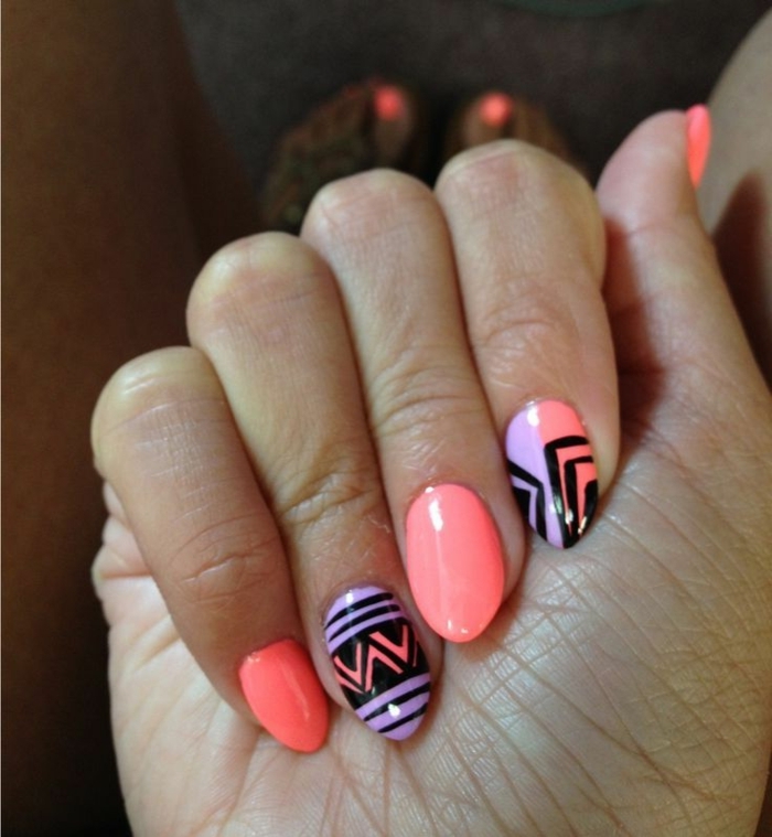 spring or summer manicure, with neon pink, and light purple nail polish, decorated with black, hand-drawn shapes, on short stiletto nails
