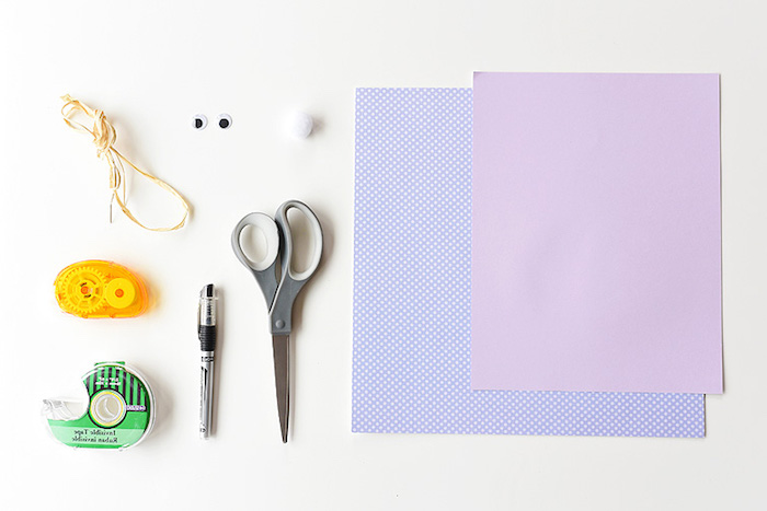 different kinds of stationary, scissors and a pen, two sticky tape dispensers, straw-like thread, eye stickers and a small cotton ball, craft ideas for kids, two sheets of plain, and patterned purple paper