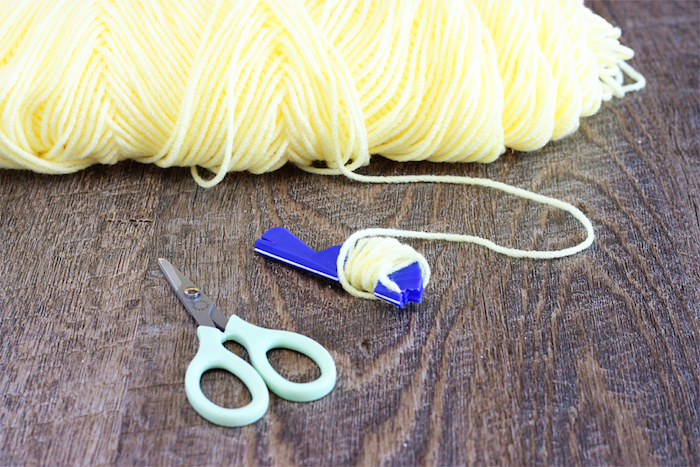 lots of pale yellow thread, some woven around a bright blue knitting tool, near pair of small light blue scissors, easter crafts for kids