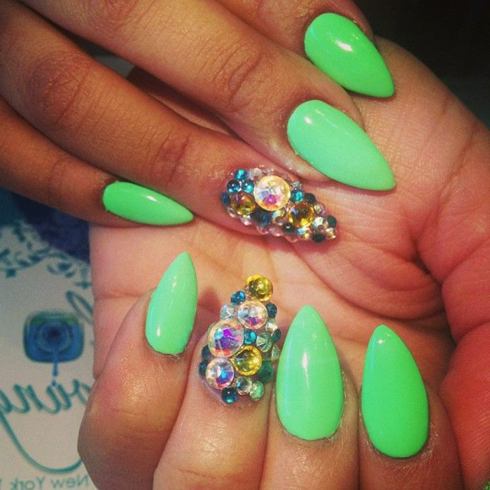 vibrant neon green nail polish, on oval sharp manicure, two of the nails are encrusted, in multicolored rhinestone gem stickers
