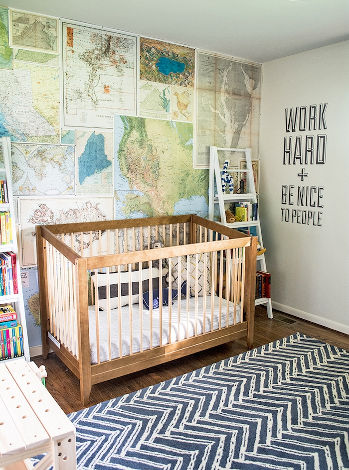 navy blue rug, with white pattern, in gender neutral nursery, one wall covered with different maps, wooden crib with white bedding