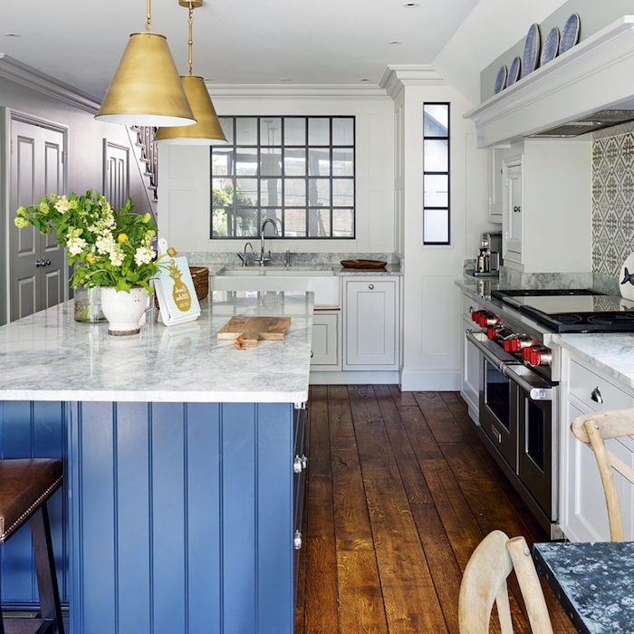marble surface in white and gray, on blue kitchen island, decorative plates and potted flowers, large stove and massive wooden floorboards, rustic country home décor