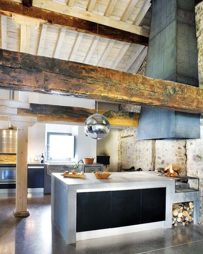 round metallic lamp, hanging from a vaulted ceiling, with wooden boards and beams, over an industrial style rustic kitchen, with fireplace and concrete kitchen island