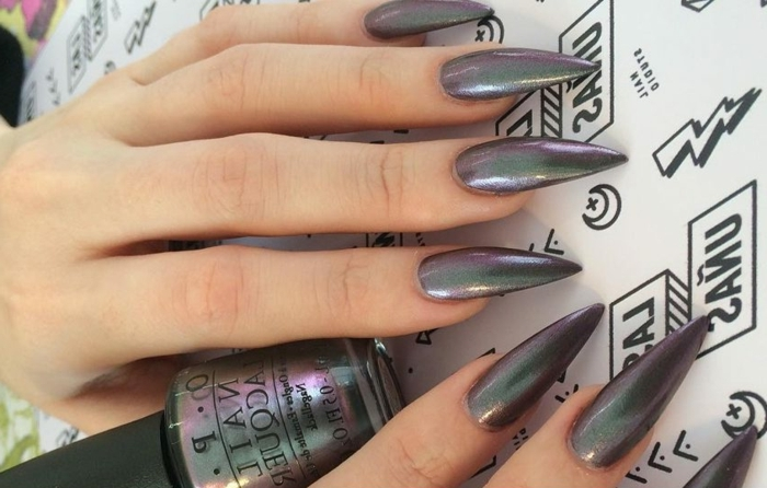 iridescent black nail polish, on long and sharp manicure, black stiletto nails, on two hands, holding a bottle of nail polish