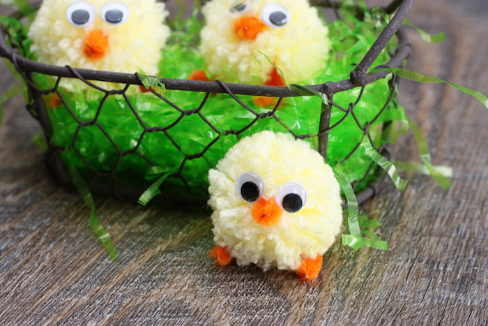 green easter grass, inside a rough metal basket, with two chick ornaments, made from pale yellow pom poms, easter crafts for kids, another chick next to the basket