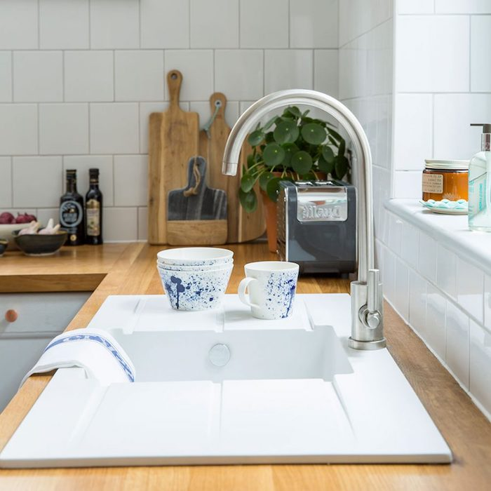 modern metal tap, on white sink, inbuilt in a light brown wooden counter, rustic country home décor, potted plant and several wooden cutting boards