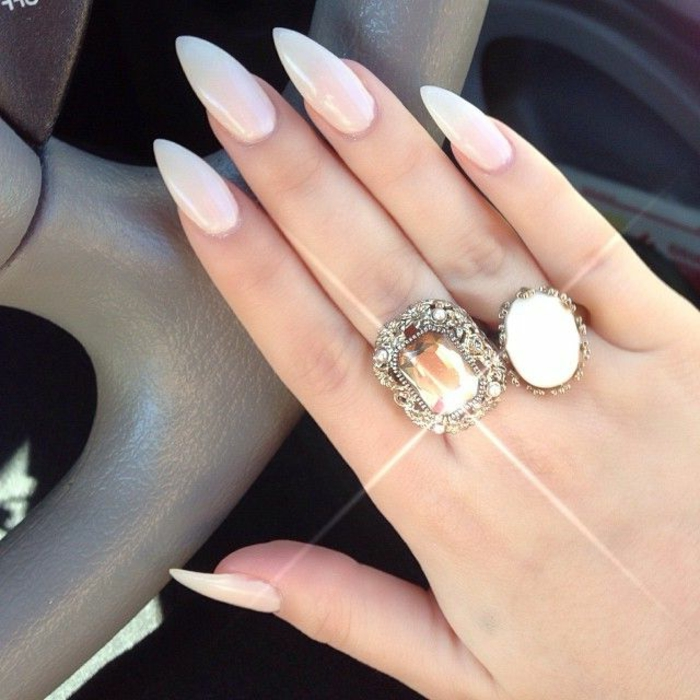 glamorous ornamental rings, on hand with long and sharp, stiletto acrylic nails, painted in milky white, semi-sheer nail polish