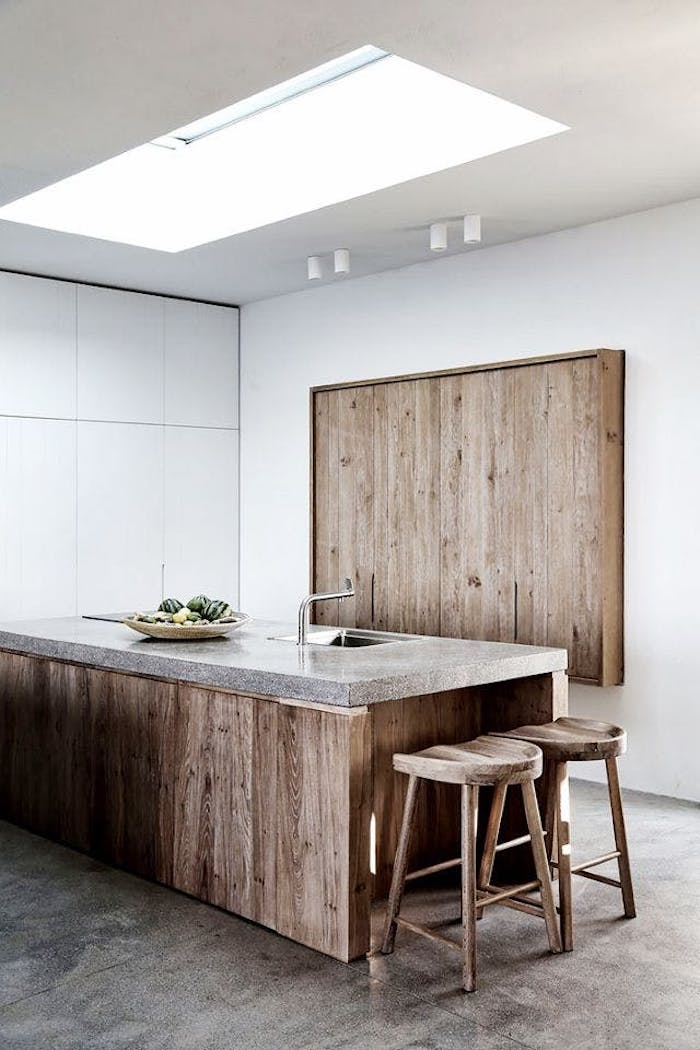 large kitchen island made of wood, with marble-like top surface, featuring an inbuilt metal sink, and a plate with fruit, two stools and a decorative wooden board nearby, rustic country home décor, white walls and minimalist aesthetic