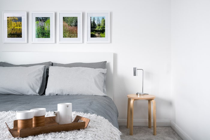 bed with covers in different shades of gray, four photographs in white frames, small wooden bedside table, colors that go with gray walls