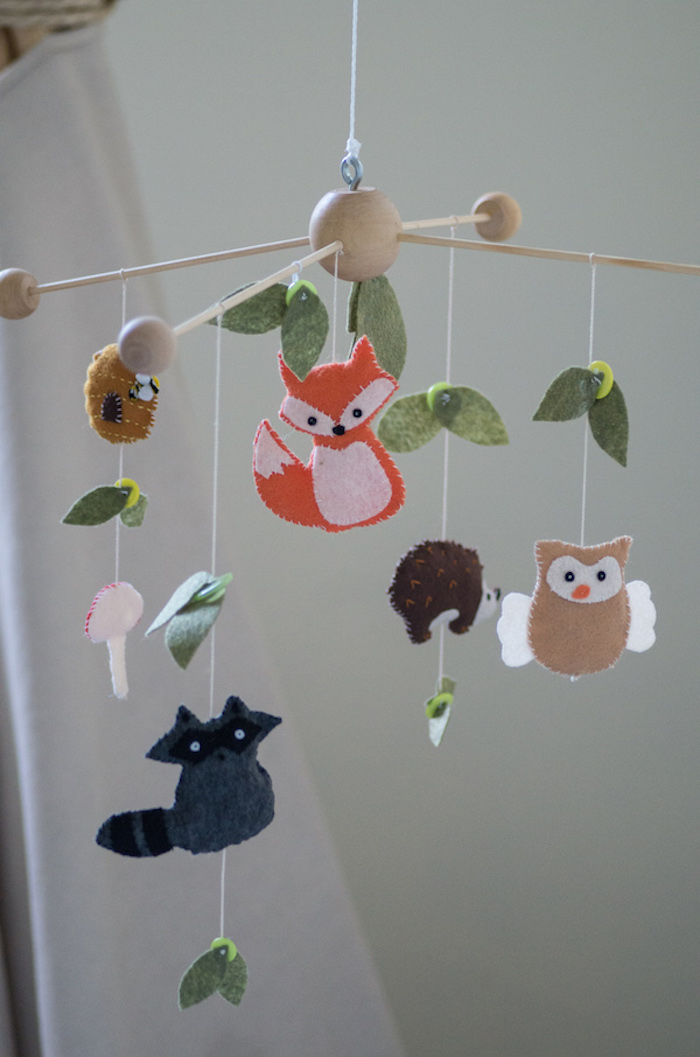 baby nursery ideas, mobile made from light wood, and decorated with leaves, animals and mushrooms, made from felt
