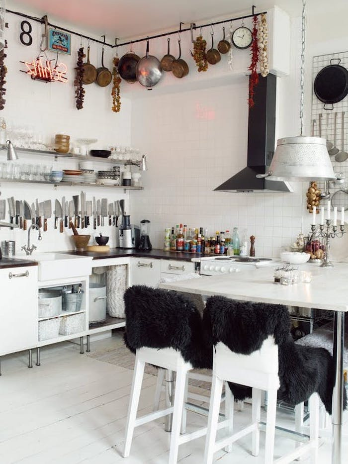 collection of cooking knives, inside room with white tiled walls, country kitchen decorating ideas, modern white table and matching chairs