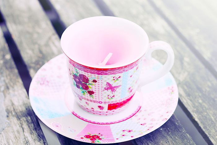 teacup with pink floral pattern, and matching saucer, containing light pink handmade candle, good mothers day gifts, rough wooden surface