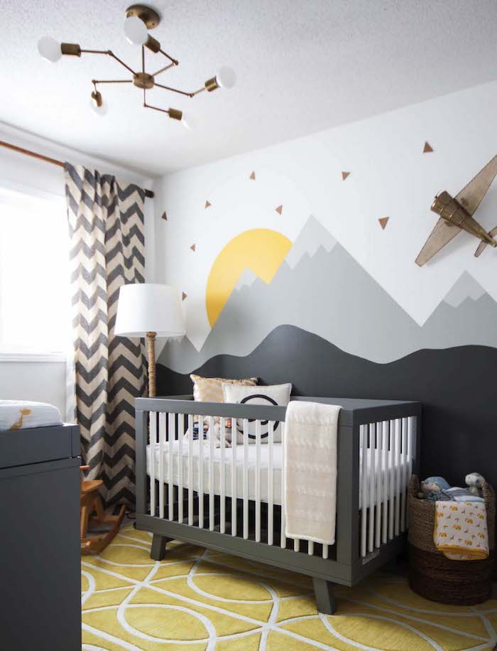 airplane near sun and mountains, painted on a white wall, in boy nursery, yellow and white carpet, black wooden crib, and matching changing table