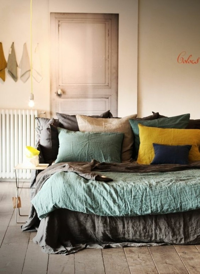 pillows in light teal and brown, dark blue yellow, on bed with matching covers, in room with light brown wooden floors, accent color with gray walls