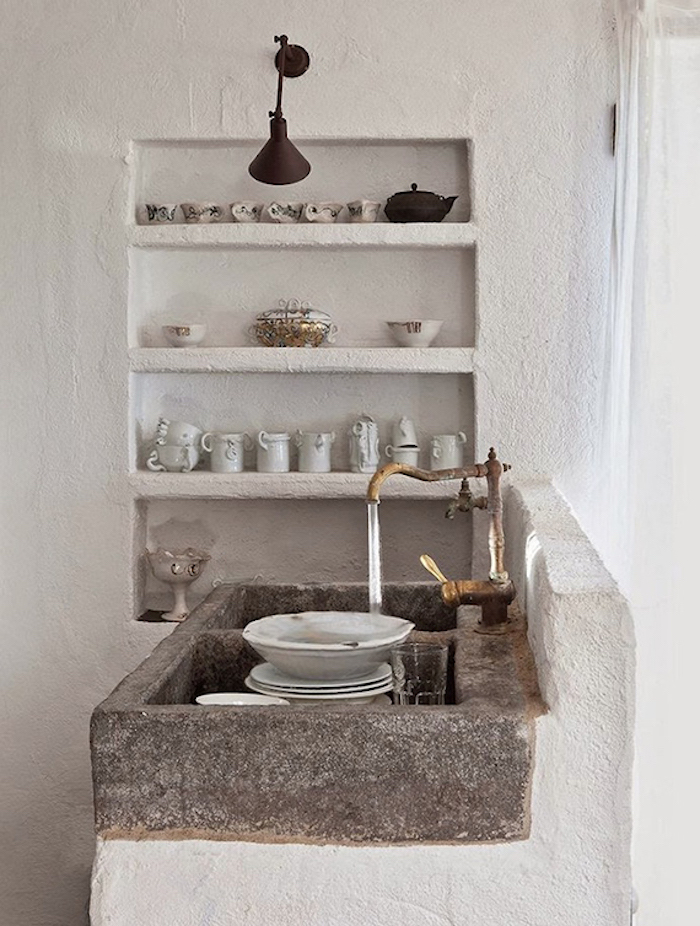 water from a brass antique tap, running over several dishes, inside a natural stone sink, rustic country home décor, lime plaster shelves, with cups and pitchers nearby