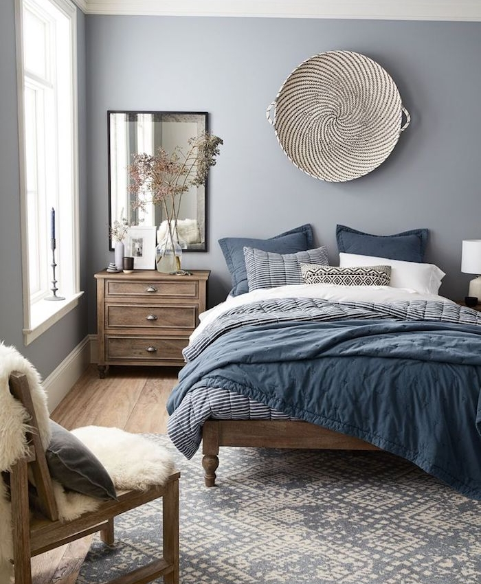 blue grey paint, in nordic style bedroom, bed covers in different shades of blue, wooden floors and furniture
