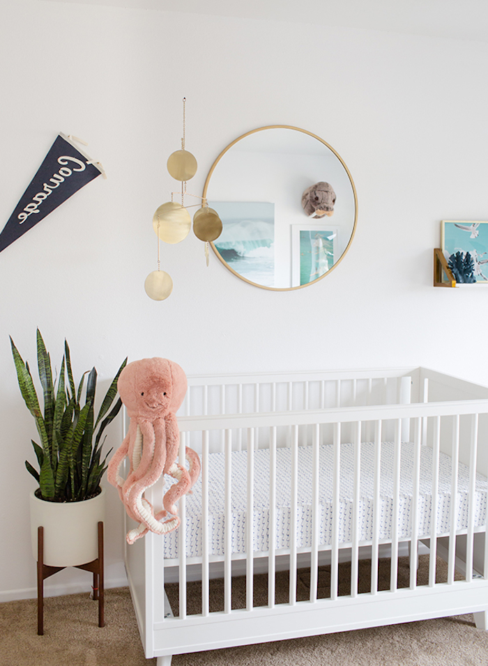octopus plush toy, on white wooden crib, in gender neutral nursery, with white walls, beige carpet and green potted plant, round mirror and other decorations