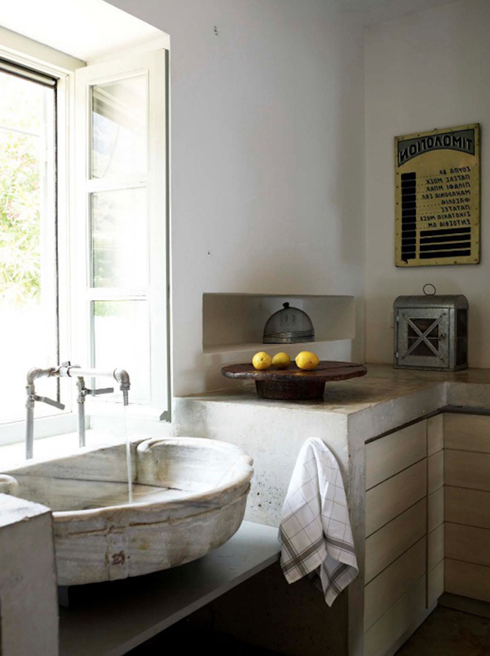 antique sink and metal tap, rustic country home décor, inside a room with industrial-style cupboards, vintage poster and metal breadbox, three lemons on a wooden dish