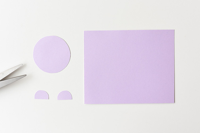 large piece of light purple paper, near three cutouts, one round and two half-circles, craft ideas for kids, near metal scissor blades