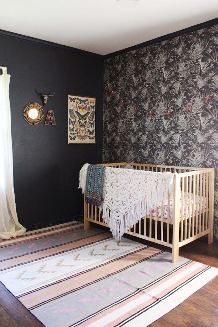 crochet blanket with tassels, on light wooden crib, in room with dark gray walls, and pastel pink, striped and patterned carpet, baby girl room décor, floral wallpaper in gray tones
