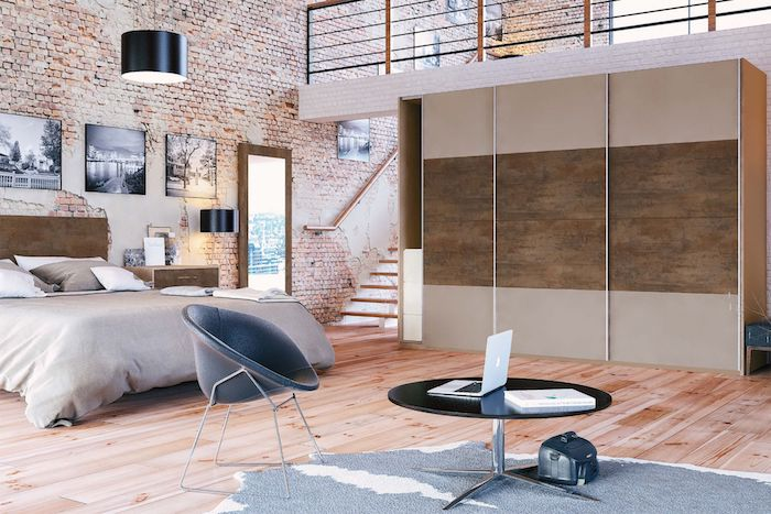 industrial style brown and grey bedroom, in open-plan penthouse flat, light laminate floor, grey animal skin rug, brick-wall design