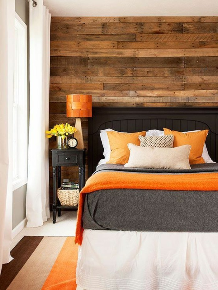 warm wooden planks, on bedroom wall, opposite wall is gray, dark grey bed, with light gray and beige, and orange bedcovers and pillows, colors that go with gray walls, striped three tonal rug