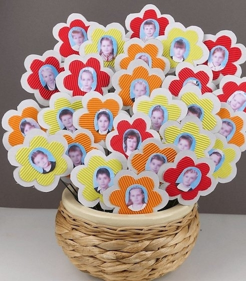 lots of flowers, made from red and orange, yellow and white paper, with wire stalks, and photos of kids and adults, mother's day gifts for grandma, inside wicker basket