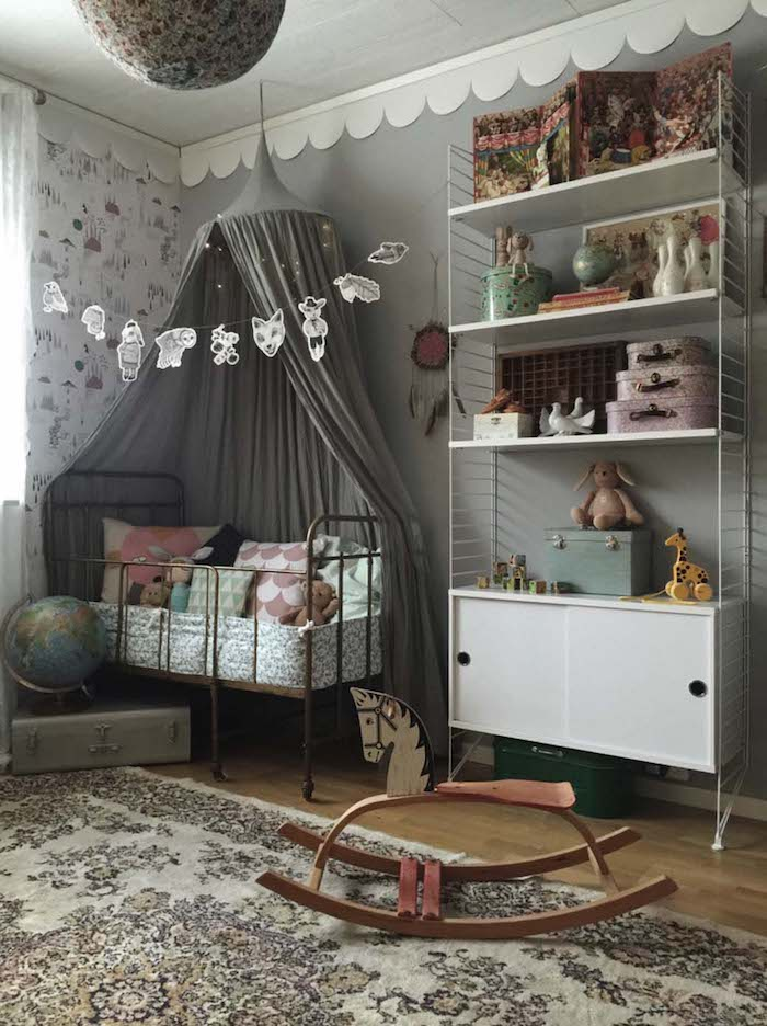 baldachin in gray, over vintage metal crib, with lots of cushions in different colors, white cupboard with shelves nearby, girl nursery themes, oriental rug and rocking horse