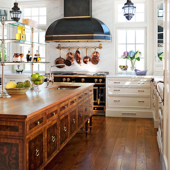 brass pots and pans, hanging over an antique black stove, with gold-colored details, near wooden country kitchen cabinets, in white and brown